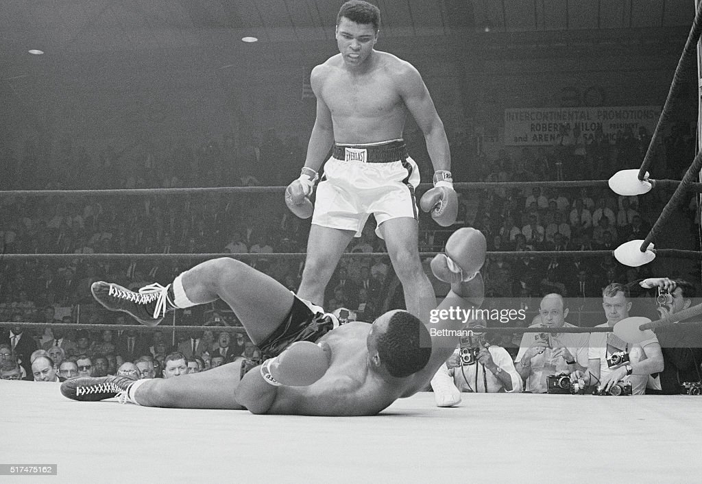 Heavyweight champion Cassius Clay stands over the downed Sonny Liston and taunts him after knocking him out in the first round of their title match May 25.