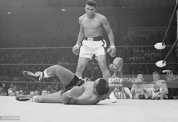 Heavyweight champion Cassius Clay stands over the downed Sonny Liston and taunts him after knocking him out in the first round of their title match...