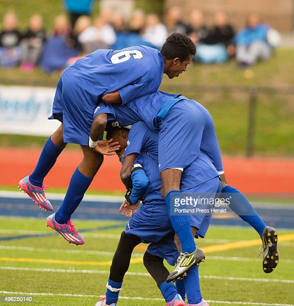 Lewiston players pile on teammate Maulid Abdow after he scored the first and only goal to beat Scarborough for the Class A state title on Saturday at...
