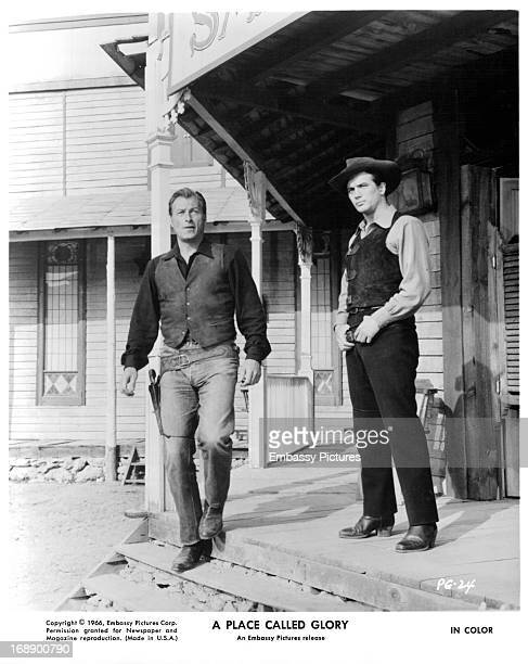 Lex Barker and Pierre Brice on a porch in a scene from the film 'A Place Called Glory' 1965