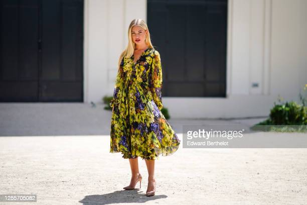 Lexi Fargo wears a green and purple long flowing ruffled dress with printed grapes and leaves from Dolce & Gabbana, pink Louboutin pointy high heeled...