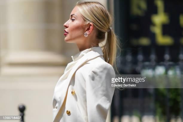 Lexi Fargo wears Chanel earrings, a white Zara jacket and blouse, on July 11, 2020 in Paris, France.