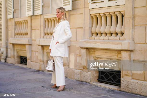 Lexi Fargo wears Chanel large golden earrings, a Chanel long necklace, a white cropped top, a white oversized blazer jacket from Zara, white pants...