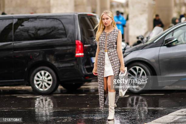 Lexi Fargo wears earrings a Chanel bag with tweed a tweed checked dress a brown turtleneck white boots outside Rokh during Paris Fashion Week...