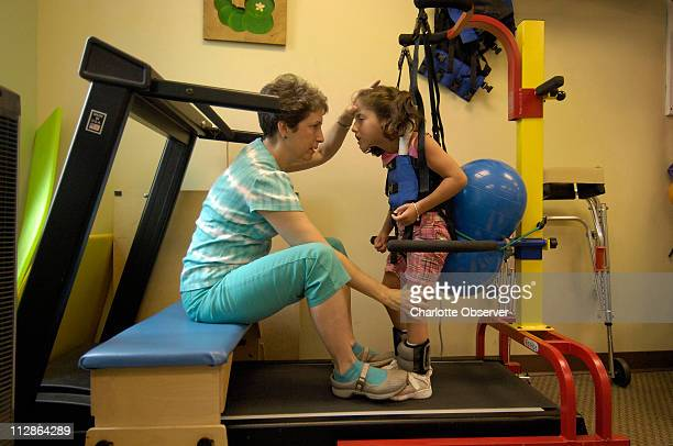 Lexi Haas right works on the treadmill during a physical therapy session with Gail Fennimore July 22 in Charlotte North Carolina Lexi has a rare form...