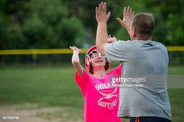 Lexi Nevells goes up for a double high five from first base coach Thomas Martel after she reached first base in a Little League softball game in...