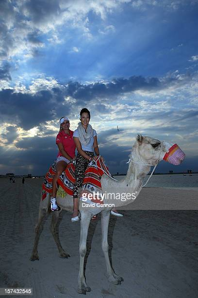Lexi Thompson of the USA and Michelle Wie of the USA riding a camel on the beach at the Jebel Ali Golf Resort and Spa as a preview for the 2012 Omega...
