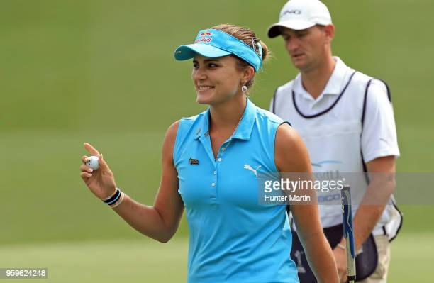 Lexi Thompson smiles as she waves to the crowd after putting out on the 18th hole during the first round of the Kingsmill Championship presented by...