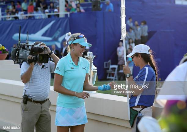 Lexi Thompson takes time to give the walking standard bearer a signed ball on the 18th green after her eagle putt to win just missed during the final...