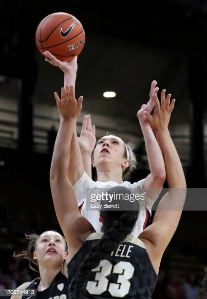 Lexie Hull of the Stanford Cardinal shoots over the defense of Peanut Tuitele and Emma Clarke of the Colorado Buffaloes during the first quarter of a...