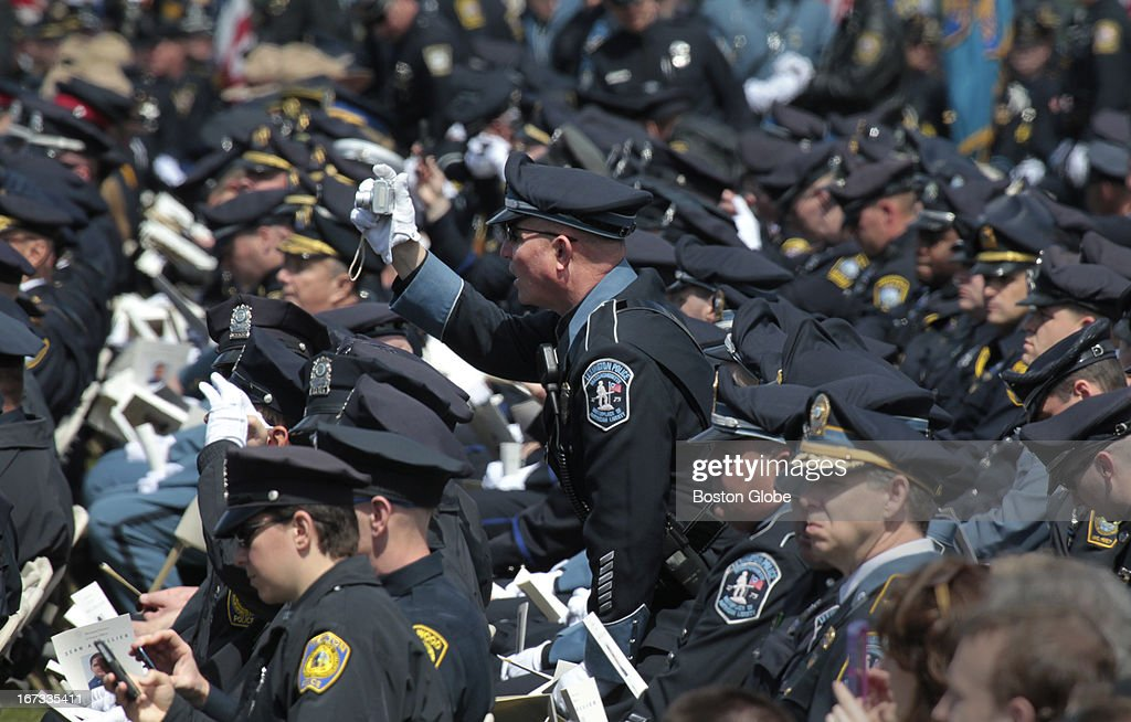 A Lexington police officer takes a picture before the memorial service for MIT police officer Sean Collier, at Briggs Field, on the MIT campus. Collier was killed during a shootout with the Boston Marathon bombing suspects.