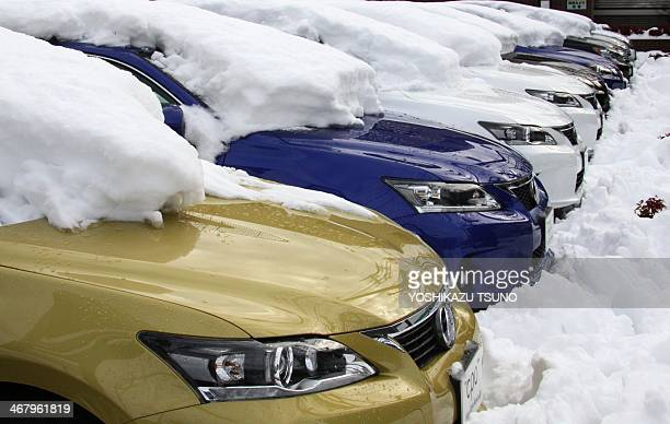Lexus vehicles are covered with snow at a vehicle shop in Tokyo on February 9 2014 one day after a heavy snowfall hit the capital The heaviest snow...