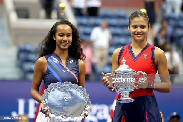 Leylah Annie Fernandez of Canada holds the runner-up trophy as Emma Raducanu of Great Britain celebrates with the championship trophy after their...