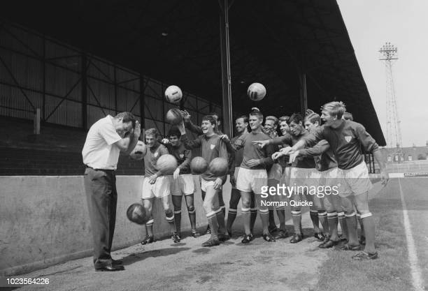 Leyton Orient FC soccer players throwing soccer balls at English manager Dave Sexton UK 6th August 1965