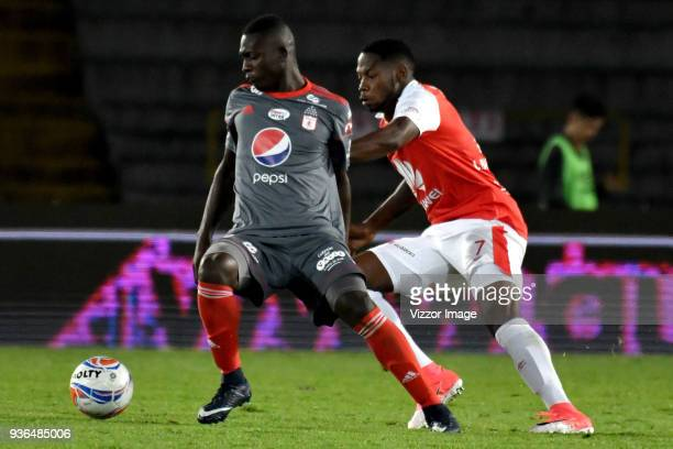 Leyvin Balanta of Independiente Santa Fe struggles for the ball with Gustavo Carvajal of America de Cali during a match between Independiente Santa...