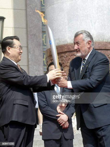 Li Changchun a member of China's politburo receives the Olympic flame from Marton Simitsek vice president of Athens Olympic Committee on the steps of...