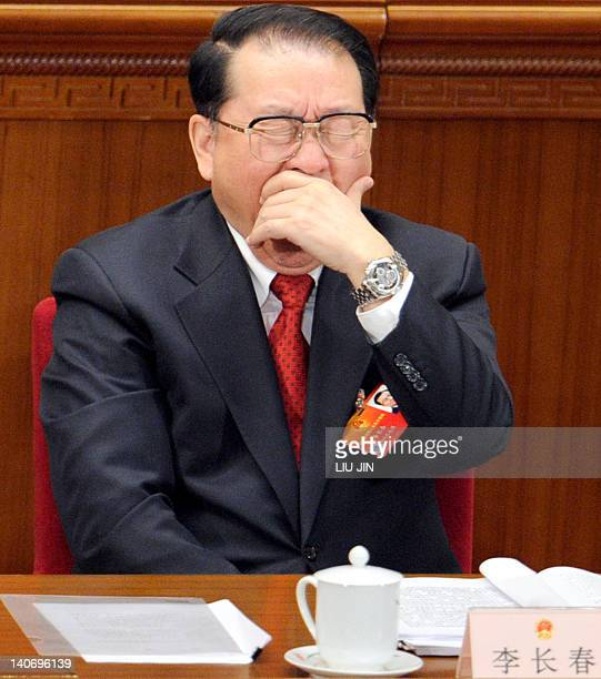 Li Changchun a member of the standing committee of the political bureau of CPC yawns during the opening session of the National People's Congress at...
