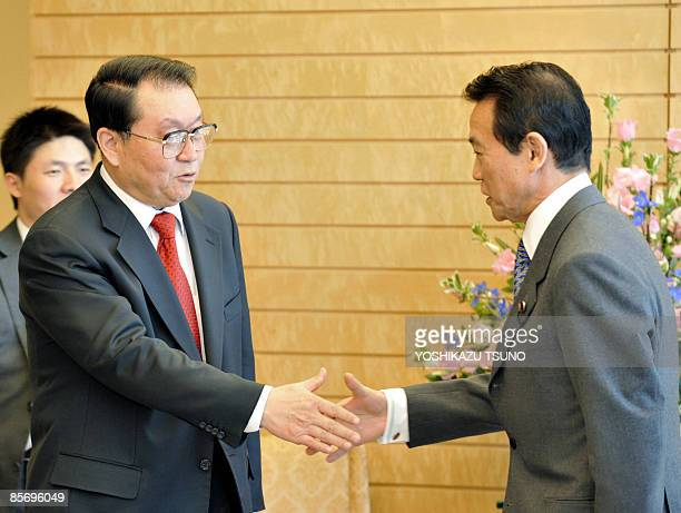 Li Changchun standing committee member of Chinese Communist Party's Political Bureau shakes hands with Japanese Prime Minister Taro Aso prior to...