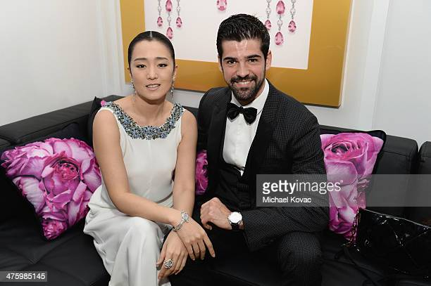 Li Gong wearing Piaget and Miguel Angel Munoz pose in the Piaget Lounge during the 2014 Film Independent Spirit Awards at Santa Monica Beach on March...