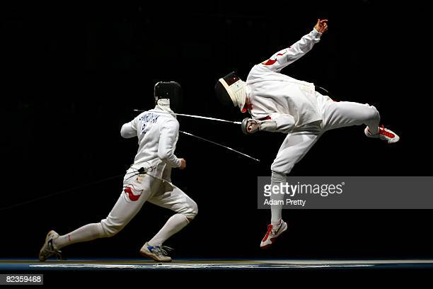 Li Guojie of China jumps up for a touch against Radoslaw Zawrotniak of Poland in the semifinal of the men's team epee fencing event at the Fencing...