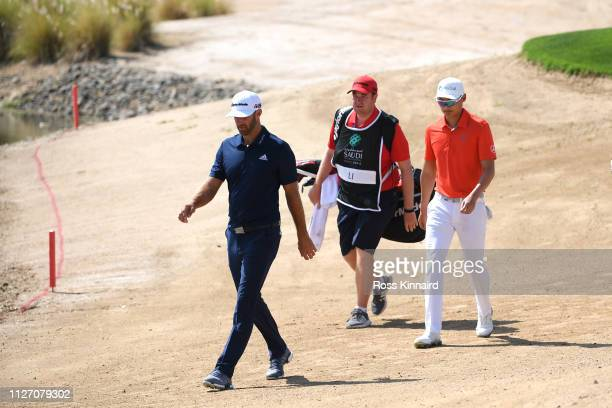 Li Haotong of China and Dustin Johnson of The United States walk on the second hole during Day four of the Saudi International at the Royal Greens...