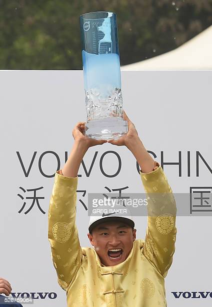 Li Haotong of China holds the trophy after winning the Volvo China Open golf tournament in Beijing on May 1 2016 / AFP / GREG BAKER