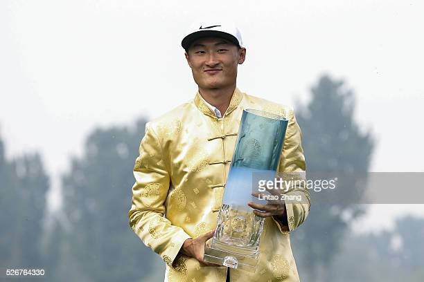 Li Haotong of China holds the trophy after winning the Volvo China Open at Topwin Golf and Country Club on May 1 2016 in Beijing China