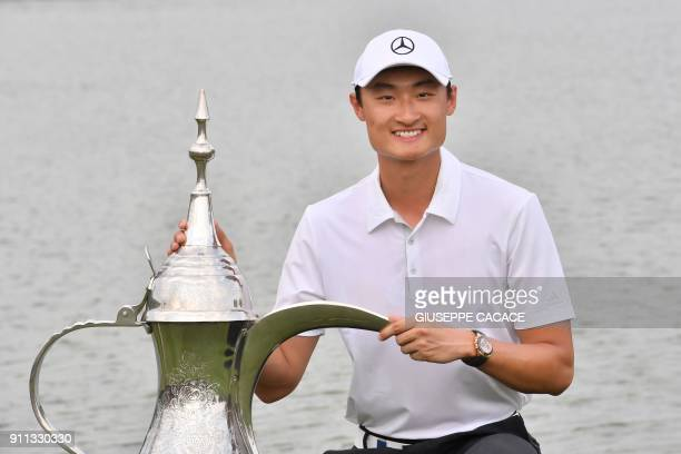 Li Haotong of China poses with the winner's trophy while celebrating his victory in the the Dubai Desert Classic at Emirates Golf Club on January 28...