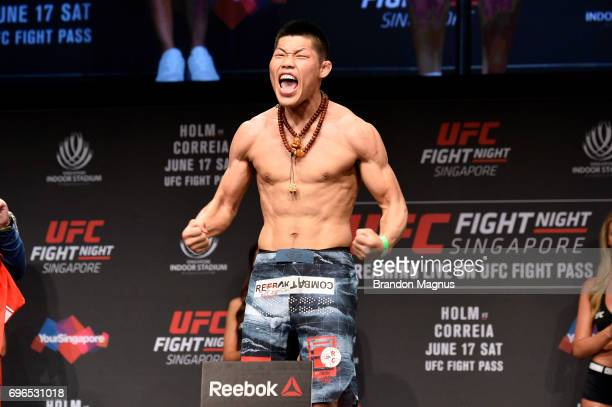 Li Jingliang of China poses on the scale during the UFC Fight Night weighin at the Marina Bay Sands on June 16 2017 in Singapore