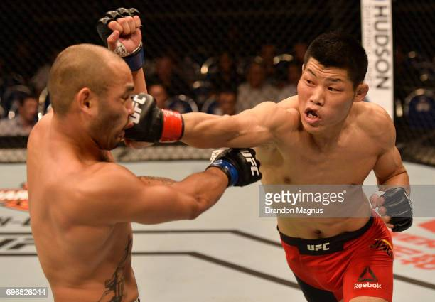 Li Jingliang of China punches Frank Camacho of the Northern Mariana Islands in their welterweight bout during the UFC Fight Night event at the...