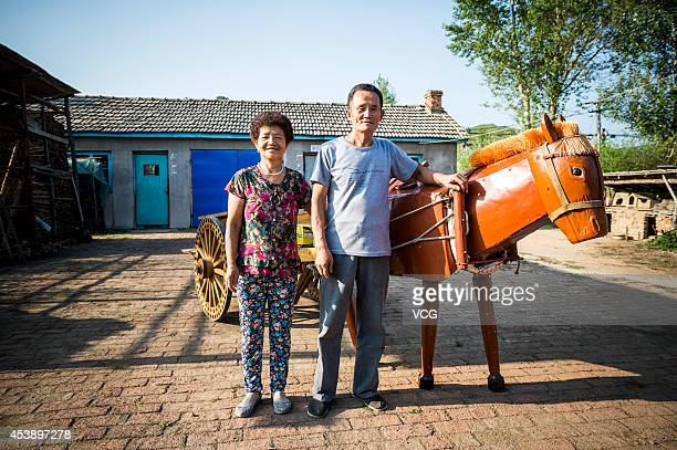 Li Jingyang a 60yearold carpenter and farmer and his wife pose with the wooden horse on August 20 2014 in Jilin China Li Jingyang a carpenter and...