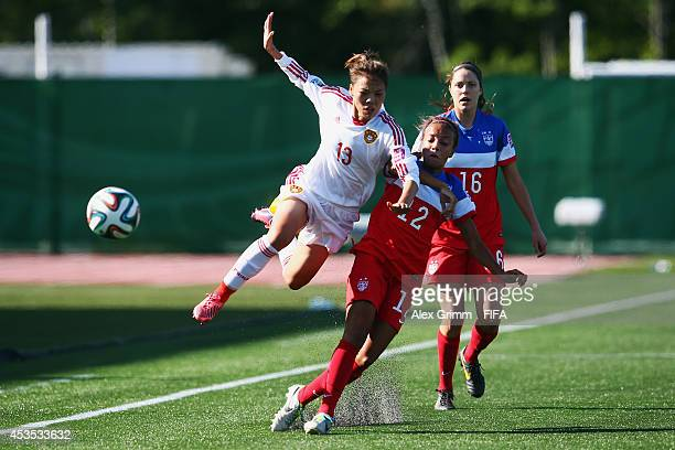 Li Mengwen of China is challenged by Mallory Pugh and Stephanie Amack of the United States during the FIFA U20 Women's World Cup Canada 2014 group B...