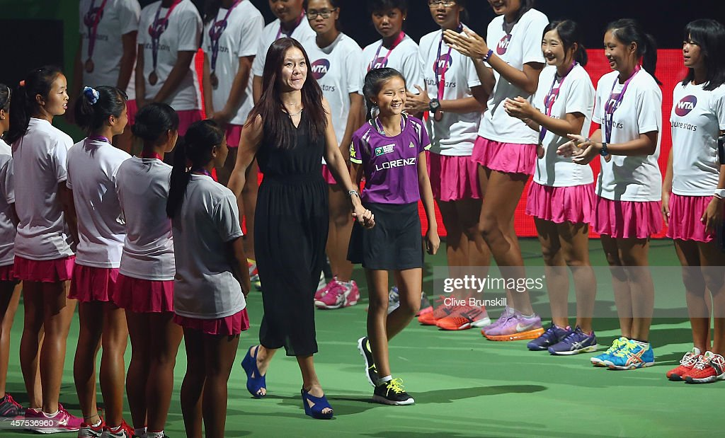 Li Na of China Ambassdor to the WTA Finals walks out on to the court to hit the opening serve at the opening ceremony prior to the start of the opening round robin match of the BNP Paribas WTA Finals at Singapore Sports Hub on October 20, 2014 in Singapore.
