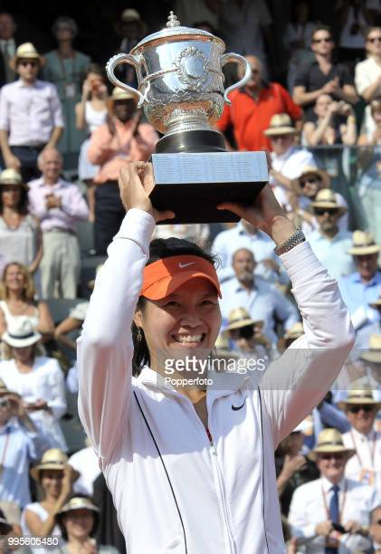 Li Na of China holds aloft the trophy after winning the Women's Singles Final in straight sets against Francesca Schiavone of Italy during day 14 of...