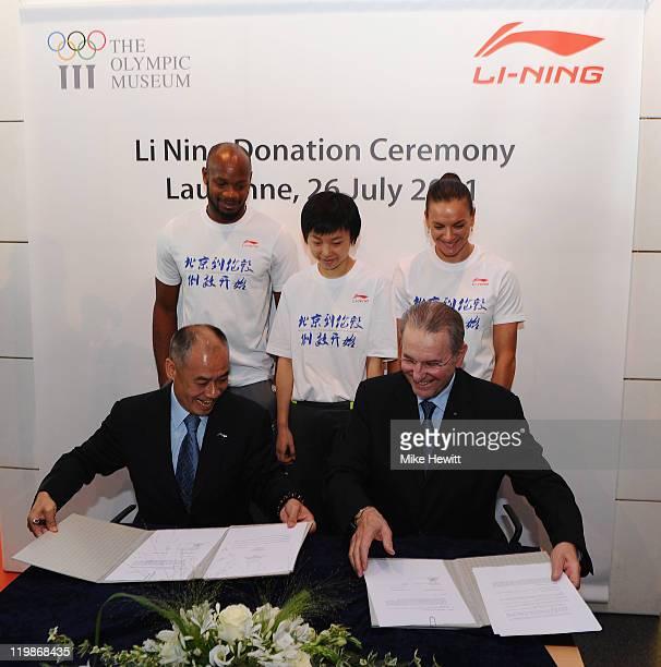 Li Ning Chairman of Li Ning and IOC President Jacques Rogge sign the agreement as Asafa Powell of Jamaica Zhang Yining of China and Yelena Isinbayeva...