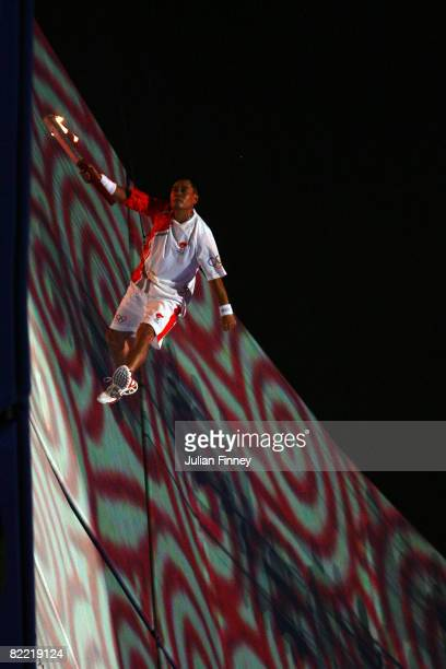 Li Ning former Olympic gymnast for China makes his way to the Olympic cauldron to light the flame during the Opening Ceremony for the 2008 Beijing...