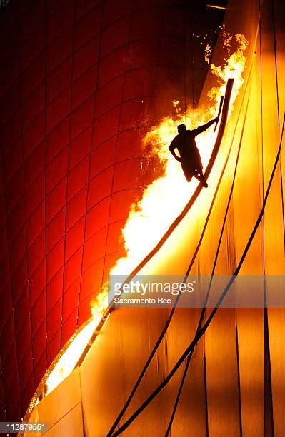 Li Ning hangs in the air and is silhouetted as he lights the flame on the top of the National Stadium during the opening ceremony on Friday August 8...