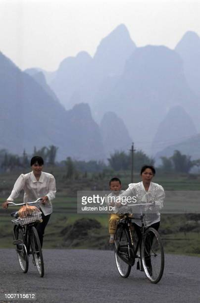 VILLAGERS CYCLING CHINA Li River Valley Two women and a child cycle in front of the valley More pictures on this subject available on request...