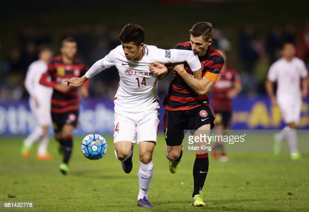 Li Shenglong of Shanghai is challenged by Shannon Cole of the Wanderers during the AFC Asian Champions League Group Stage match between the Western...