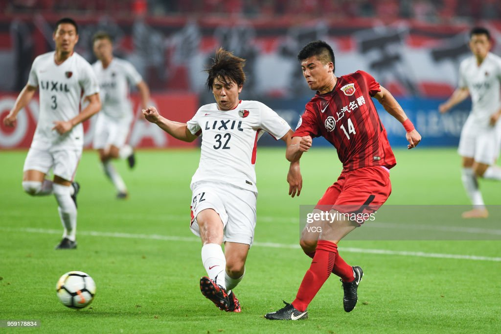 Li Shenglong #14 of Shanghai SIPG and Koki Anzai #32 of Kashima Antlers compete for the ball during the AFC Champions League Round of 16 second leg match between Shanghai SIPG and Kashima Antlers at Shanghai Stadium on May 16, 2018 in Shanghai, China.
