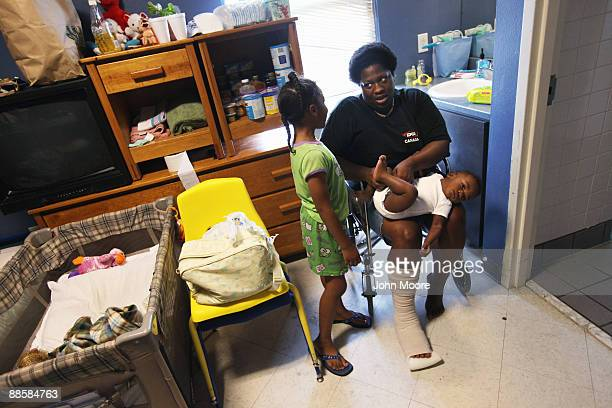 Li Tina Cross finishes changing her son De Rylon Davis' diaper while talking with her daughter T-Kyler Davis at the Presbyterian Night Shelter on...