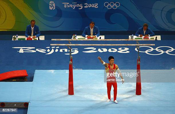 Li Xiaopeng of China celebrates after his dismount from the Paralle Bars in the men's team final of the artistic gymnastics event held at the...