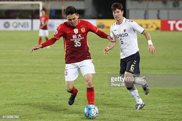 Li Xuepeng of Guangzhou Evergrande in action against Kim Junsu of Pohang Steelers during the AFC Champions League match between Guangzhou Evergrande...