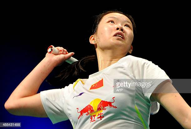 Li Xuerui of China jumps for a smash against Saina Nehwal of India during their women's singles at the BWF badminton World Superseries Finals in...