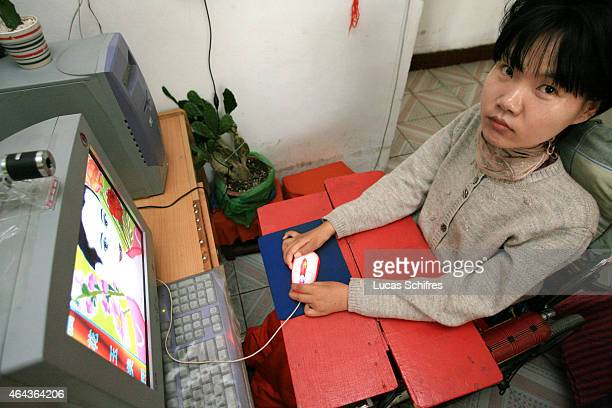 Li Yan operates her computer with the sole four fingers that she can move in her home on May 7 2007 in Yinchuan Ningxia Province China Li Yan spends...