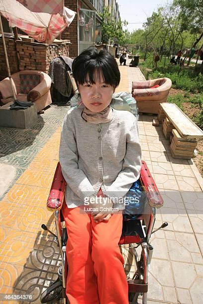 Li Yan sits in a wheelchair in front of her home on May 7 2007 in Yinchuan Ningxia Province China 28yearold Li Yan suffers from motor neuron disease...