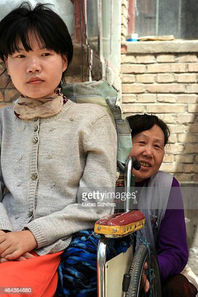 Li Yan sits in her wheelchair while her mother Song Fengying seats behind it outside their house on May 7 2007 in Yinchuan Ningxia Province China...
