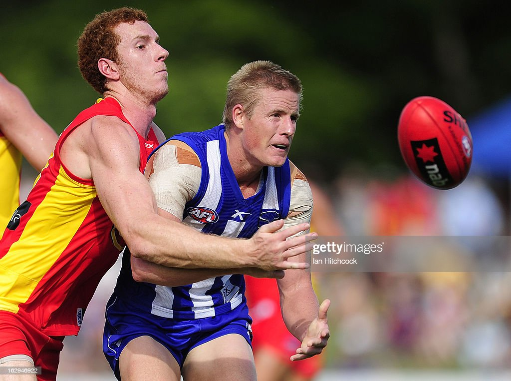 Liam Anthony of the Kangaroos gets a handball away despite being tackled by Rory Thompson of the Sunsduring the round two AFL NAB Cup match between the Gold Coast Suns and the North Melbourne Kangaroos at Tony Ireland Stadium on March 2, 2013 in Townsville, Australia.