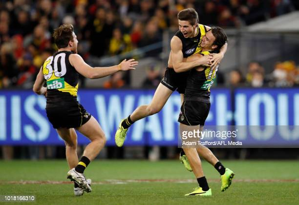 Liam Baker of the Tigers celebrates his first AFL goal with Reece Conca and Daniel Rioli of the Tigers during the 2018 AFL round 22 match between the...