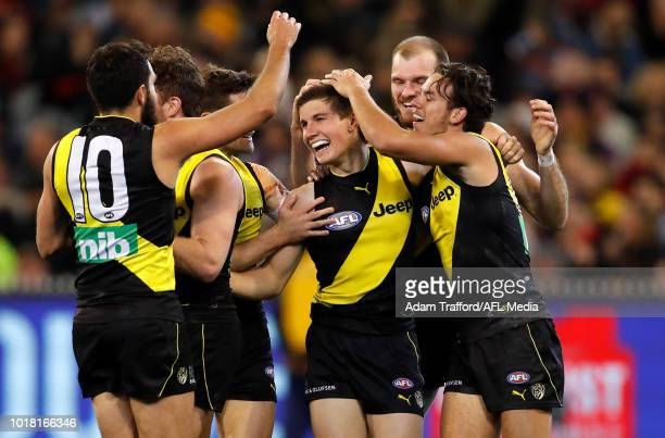 Liam Baker of the Tigers celebrates his first AFL goal with teammates during the 2018 AFL round 22 match between the Richmond Tigers and the Essendon...